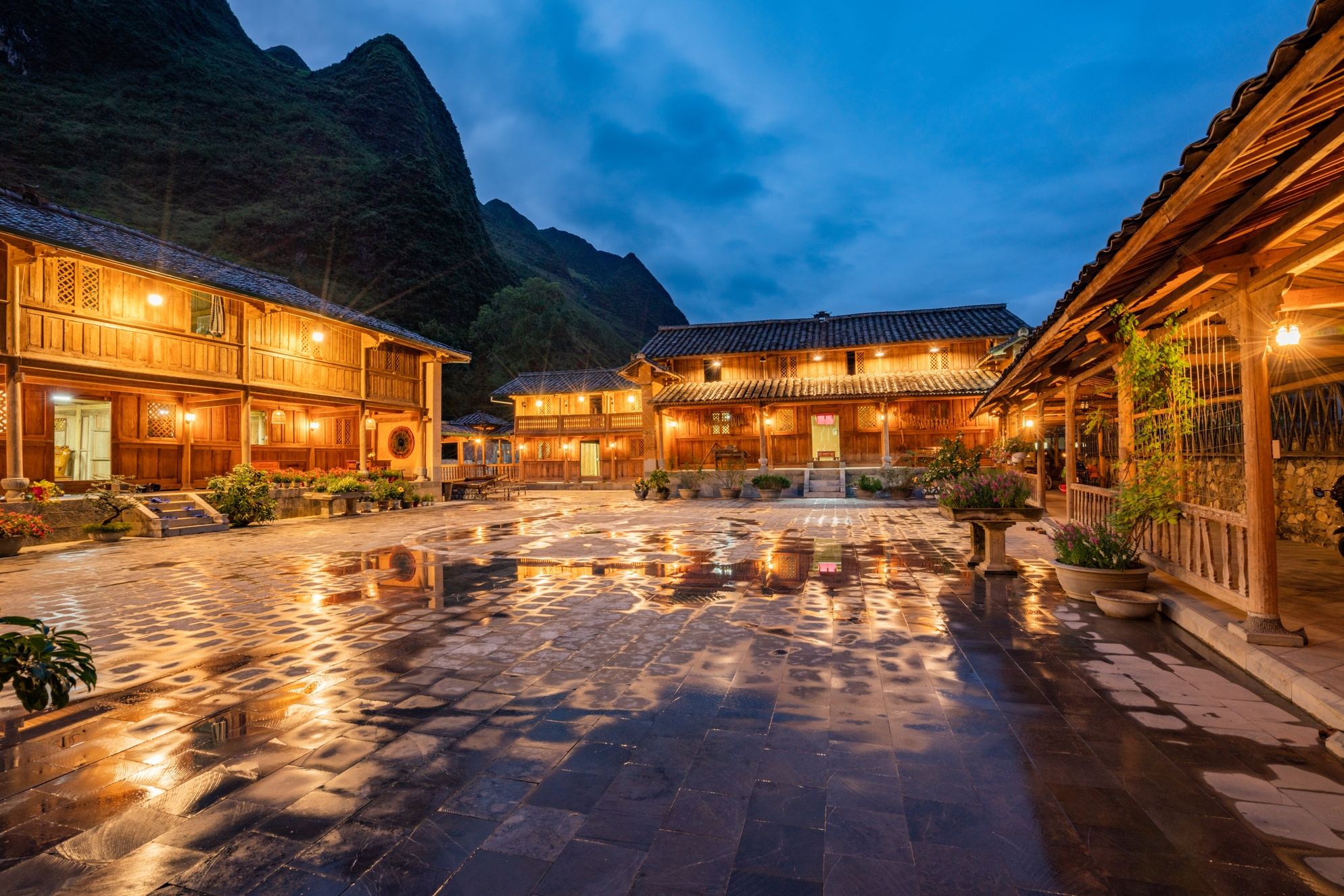 Wide shot of an estate with wooden cabins surrounded by high mountains at night